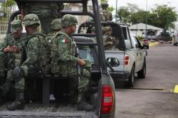 Mexican soldiers ride in the back of a pick up truck as they escort the caravan carrying Mexico's Minister of Defense, in Tapachula, Mexico, Tuesday, June 11, 2019