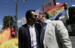 Javier Benalcazar, left, and his partner Efrain Soria kiss as they arrive outside the Constitutional Court to hear the final decision on same sex marriage, in Quito, Ecuador.