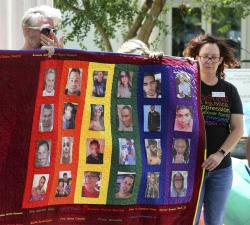 Douglas Barrett, left, and Rev. Shelly Denmark, with others, hold a memorial quilt during the tolling of the bells and reading of the names at First United Methodist Church in Orlando, Fla.