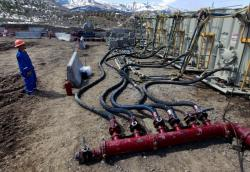 In this March 29, 2013, file photo, a worker helps monitor water pumping pressure and temperature, at an oil and natural gas extraction site, outside Rifle, on the Western Slope of Colorado