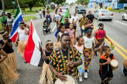 In this June 19, 2018, file photo, Zebiyan Fields, 11, at center, drums alongside more than 20 kids at the front of the Juneteenth parade in Flint, Mich.