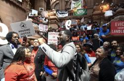 In this June 4, 2019 file photo, Jumaane Williams, Public Advocate for the City of New York, center, speaks with tenants and members of the Upstate Downstate Housing Alliance from across the state, demanding New York Gov. Andrew Cuomo and state legislators pass universal rent control legislation during a protest rally at the state Capitol in Albany, N.Y.