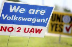 Signs for and against unionization are in a roundabout along Volkswagen Drive in front of the Volkswagen plant Friday, June 14, 2019 in Chattanooga, Tenn.