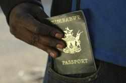 A man puts an expired passport in his pocket while waiting in a queue to submit an application for a new passport at the main office in Harare, Friday, June 14, 2019