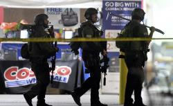 Heavily armed police officers exit the Costco following a shooting inside the wholesale warehouse in Corona, Calif., Friday, June 14, 2019