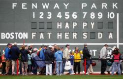 In this June 21, 2009 file photo, fans tour in front of the scoreboard in Fenway Park in Boston in celebration of Father's Day following a baseball game between the Atlanta Braves and the Boston Red Sox