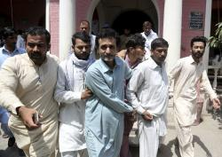 In this May 15, 2019, photo, officials of Pakistan's Federal Investigation Agency escort detain criminals allegedly involved in a trafficking gang to lure Pakistani women into fake marriages, to a court in Faisalabad, Pakistan