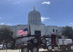 In this June 12, 2019, file photo, a truck moves around the Oregon state Capitol during a protest against climate bills that truckers say will put them out of business, in Salem, Ore.