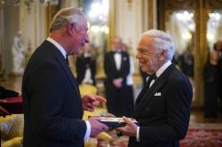 The Prince of Wales presents designer Ralph Lauren with his honorary KBE (Knight Commander of the Order of the British Empire).