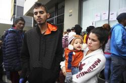 Venezuelan migrant couple Johan Alvarez and Daniela Tovar, with their son Matias, speak during an interview outside a refugee office run by Peru's Special Commission for Refugees Executive Secretariat, where they wait to apply for refugee status in Lima, Peru, Tuesday, June 18, 2019
