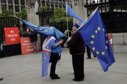 Anti-Brexit remain supporters stand with European flags and pro-Brexit leave supporters hold red placards as they all protest outside the Houses of Parliament in London, Wednesday, June 19, 2019