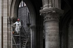 In this May 15, 2019 file photo, a worker stands on scaffolding during preliminary work inside the Notre Dame de Paris Cathedral, in Paris