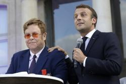 French President Emmanuel Macron, right, and Sir Elton John address the crowd in the courtyard of the presidential Elysee Palace in Paris.