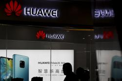In this May 29, 2019 file photo, a man walks past a Huawei retail store in Beijing