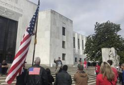 In this photo taken Sunday, June 23, 2019, a small crowd of local Republicans show their support of a Republican walkout outside the Oregon State Capitol in Salem, Ore.