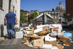 A man walks past a pile of garbage as St. Peter's Dome is visible in background, in Rome.