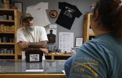 In this photo taken Tuesday, June 11, 2019, Chris Puehse, left owner of Foothill Ammo helps a customer at his shop in Shingle Springs, Calif.