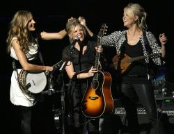 Emily Robison, left, and Martie Maguire, right, adjust Natalie Maines' hair as the Dixie Chicks perform at the new Nokia Theatre in Los Angeles in 2007.