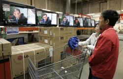 """Shoppers watch the television show """"The Office"""" as they compare wide screens on display at Costco in Mountain View, Calif."""
