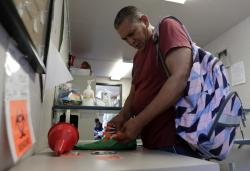 Jose Garcia, an injection drug user, deposits used needles into a container at the IDEA exchange, in Miami.