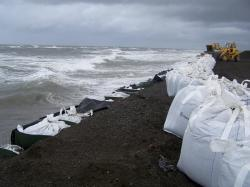 In this Sept. 13, 2007, file photo, sandbags are stacked along the seawall in Kivalina, Alaska. Northern Alaska coastal communities and climate scientists say sea ice disappeared far earlier than normal this spring and it's affecting wildlife