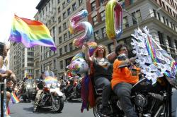 "Tina Cole, holding ""50"" balloons, sits behind her wife, Joann Bertone, as drive down New York's Fifth Avenue during the NYC Pride March."