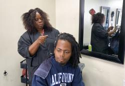 "Charlotte ""Peaches"" Smith, owner of the Dreadlocks Salon, works on a customer's dreadlocks."