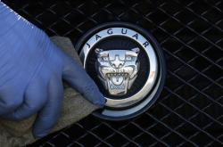 In this file photo dated Wednesday, Sept. 28, 2016, a worker polishes a Jaguar logo on a car at a Jaguar dealer outlet in London