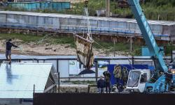In this Thursday, June 20, 2019 file photo, workers move a whale by a crane in Srednyaya Bay, out of Vladivostok, Russia