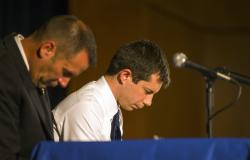 Democratic presidential candidate and South Bend Mayor Pete Buttigieg, right, and South Bend Police Chief Scott Ruszkowski, left, bow their heads in prayer during a town hall community meeting at Washington High School in South Bend, Ind.