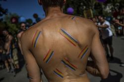 A reveller, with the rainbow flag colors painted on his back, attends the annual LGBTQ pride parade in Madrid, Spain.