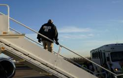 In this Nov. 16, 2018, file photo, an officer watches as immigrants who entered the United States illegally are deported on a flight to El Salvador by U.S. Immigration and Customs Enforcement in Houston