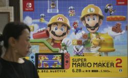 A woman walks by an advertisement poster of a Nintendo in Tokyo in Tokyo, Tuesday, July 9, 2019
