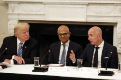 In this June 19, 2017, file photo President Donald Trump, left, and Satya Nadella, Chief Executive Officer of Microsoft, center, listen as Jeff Bezos, Chief Executive Officer of Amazon, speaks during an American Technology Council roundtable in the State Dinning Room of the White House in Washington