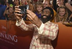 """Donald Glover takes a selfie with fans as he arrives at the world premiere of """"The Lion King"""" on Tuesday, July 9, 2019, at the Dolby Theatre in Los Angeles."""