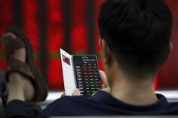 A man checks stock prices through his smartphone at a brokerage house in Beijing, Thursday, July 11, 2019