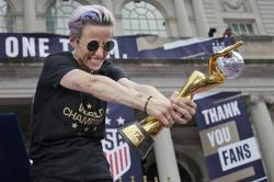 U.S. women's soccer player Megan Rapinoe celebrates with the FIFA Women's World Cup trophy at City Hall after a ticker tape parade in New York.