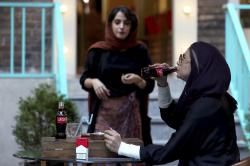 An Iranian drinks a Coca-Cola and smokes a Marlboro cigarette at a cafe in downtown Tehran, Iran.