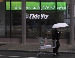In this June 18, 2019, photo a man pulls a grocery cart as he walks in the rain past the stock ticker scroll board, showing a strong daily gain in the Dow Jones, outside Fidelity Investments in the Financial District of Boston