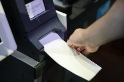 In this June 13, 2019, photo, Steve Marcinkus, an Investigator with the Office of the City Commissioners, demonstrates the ExpressVote XL voting machine at the Reading Terminal Market in Philadelphia