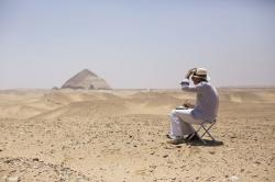 A member of an international delegation sketches the site of the Bent Pyramid during an event opening the pyramid and its satellites for visitors in Dashur, Egypt, Saturday, July 13, 2019