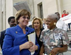 In this April 20, 2004 file photo, Rep. Carla Blanchard Dartez, D-Morgan City, center covers Gov. Kathleen Blanco, left, as a few drops of rain fall while talking with Sadie Roberts-Joseph, right, before the start of the Stand Up for Children 2004 Rally for Children on the steps of the State Capitol in Baton Rouge, La.