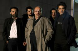 """This undated promotional handout still from the Iranian state TV series, """"Gando,"""" shows actor Payam Dehkordi, center, who plays a character apparently based on Washington Post journalist Jason Rezaian, among other actors"""