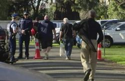 In this image made from video, people bring their guns to exchange for money in Christchurch, New Zealand Saturday, July 13, 2019