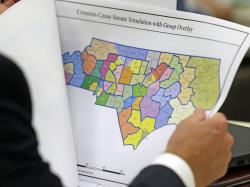 In this photo taken Wednesday, July 26, 2017 a lawmaker studies a district map during a joint select committee meeting on redistricting in Raleigh, N.C.