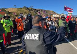 A police officer gestures at demonstrators blocking a road at the base of Hawaii's tallest mountain, Monday, July 15, 2019, in Mauna Kea, Hawaii, who are protesting the construction of a giant telescope on land that some Native Hawaiians consider sacred