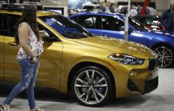 In this March 28, 2019, file photo a car shopper looks over a BMW X2 at the auto show in Denver