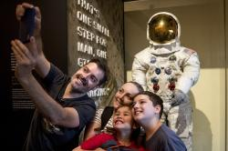 Rafiel Santos and Silvia Freddo, and their two children Jose Eduardo, 11, right, and Gustavo, 6, bottom, of Santa Catarina, Brazil, take a selfie as some of the first visitors to view Neil Armstrong's Apollo 11 spacesuit after it is unveiled at the Smithsonian's National Air and Space Museum on the National Mall in Washington.