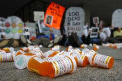Containers depicting OxyContin prescription pill bottles lie on the ground in front of the Department of Health and Human Services' headquarters in Washington