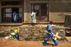 A morgue employee walks with a cross past others disinfecting the entrance to the morgue in Beni, Congo DRC.